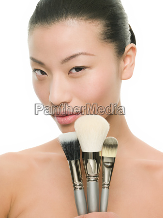 woman holding makeup brushes