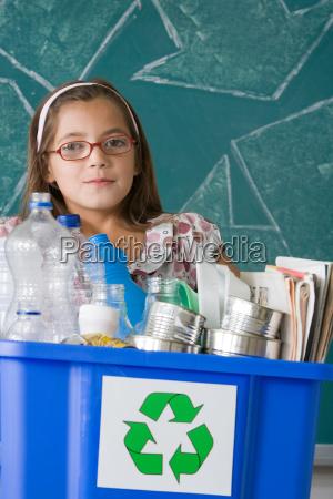 girl holding a recycling bin