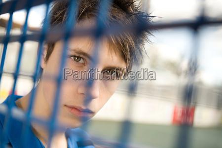 teenage boy behind fence