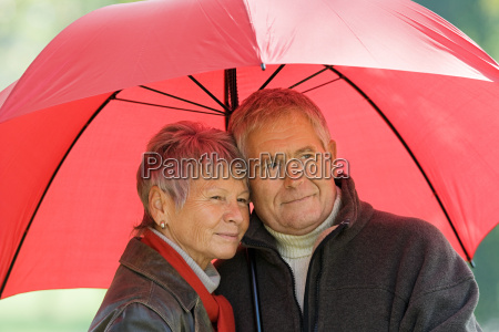senior couple using a red umbrella
