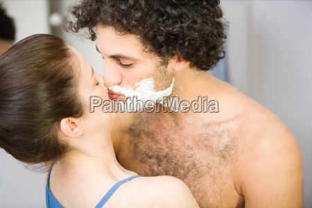 woman kissing man with shaving foam