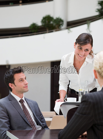 a waitress serving business people