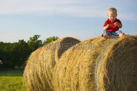 baby boy sitting on a haystack