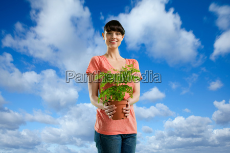 young woman holding plant against blue