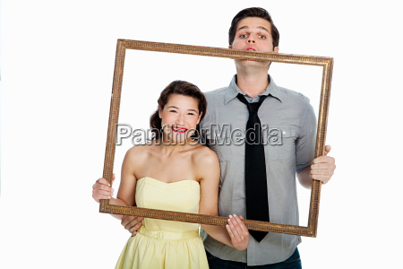 young couple holding picture frame against