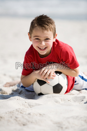 young boy holding football on a