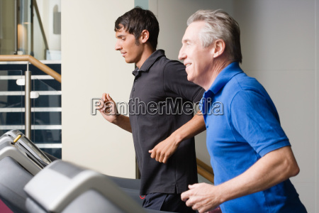 two men running on a treadmill