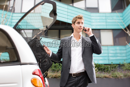 man on cellphone by car