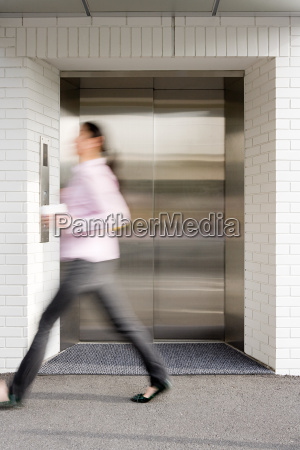 blurred woman walking past elevator