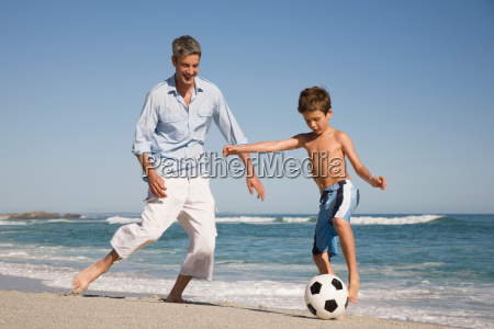 father and son playing football by