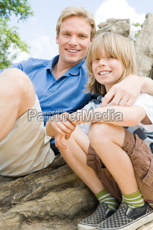boy and father sitting on tree