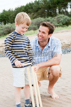 father and son on beach with