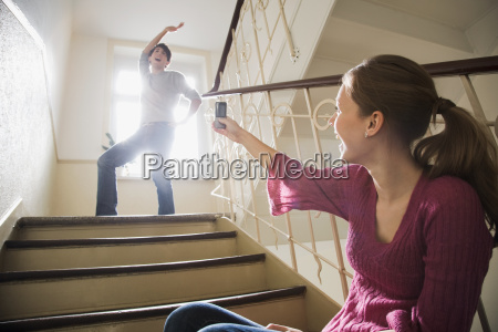 teenage girl photographing young man on