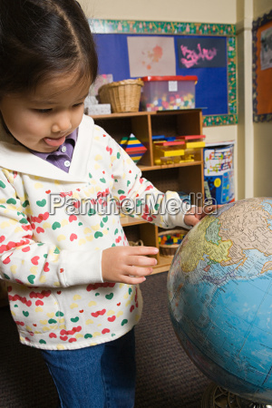 a girl looking at a globe