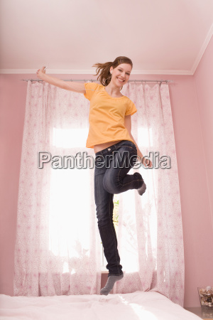 a teenage girl jumping on her