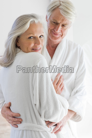 middle aged couple in bathrobes hugging
