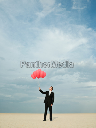 businessman holding a bunch of red