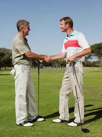 two mature men shaking hands on