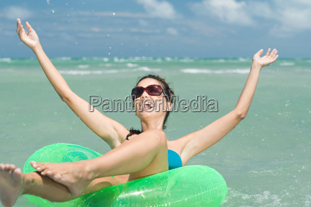 happy woman in sea on inflatable