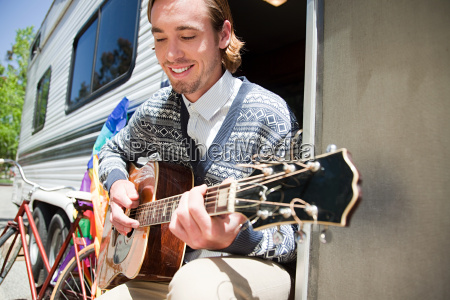 young man playing guitar by caravan