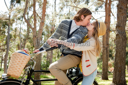 young couple kissing on bicycle