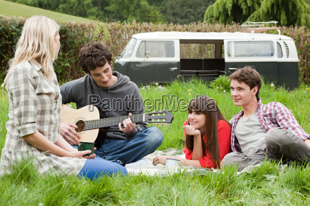 young man playing guitar for friends