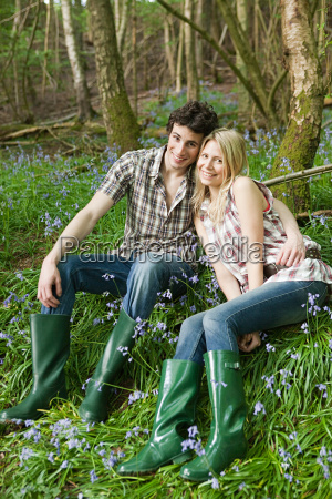 young couple sitting amongst bluebells
