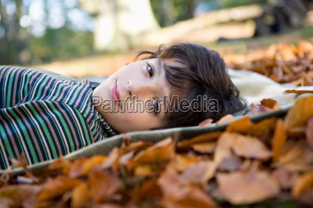 boy lying on leaves