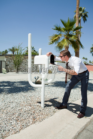 man looking into mailbox