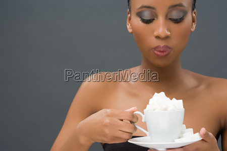 woman holding a cup of sugar