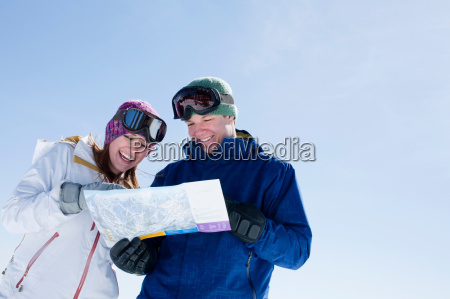 young couple holding ski map