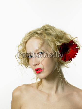 young woman wearing red flower in