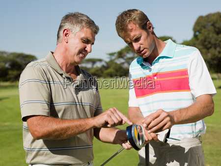 two mature men playing golf together