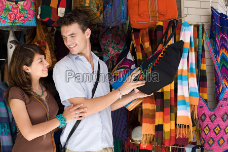 couple looking at bag on stall
