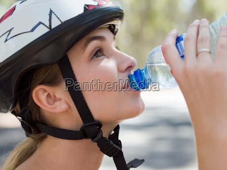young female cyclist drinking water
