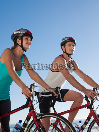 young couple cycling at beach