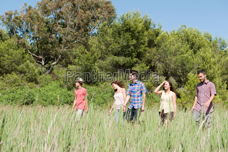 young friends walking through field