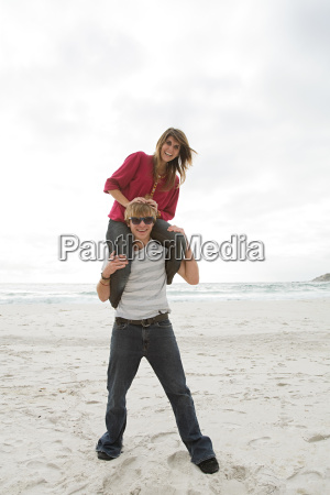 young man carrying girl on shoulders