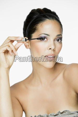 glamorous woman applying mascara