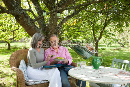 mature couple sitting on chairs outdoors