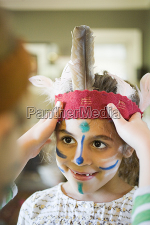 girl putting native american headdress on