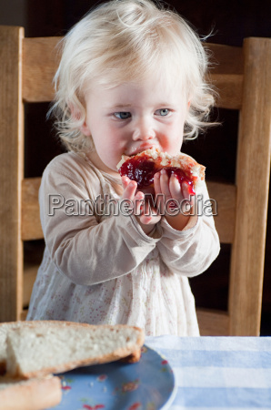 female toddler eating bread and jam