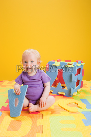 baby girl playing with toy alphabet