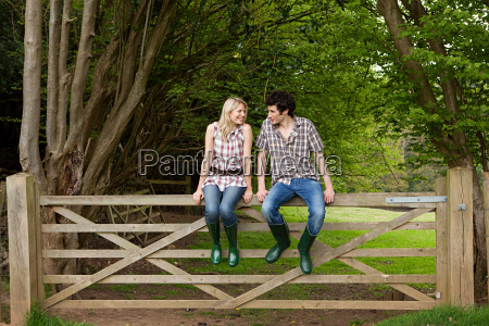young couple sitting on gate