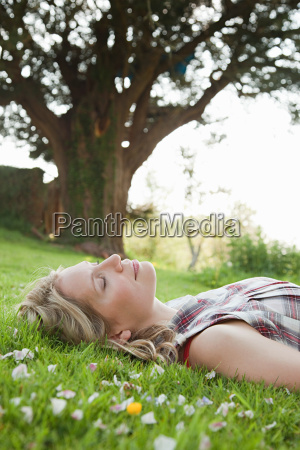 young woman lying on grass with
