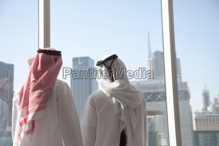 middle eastern businessmen looking at dubai