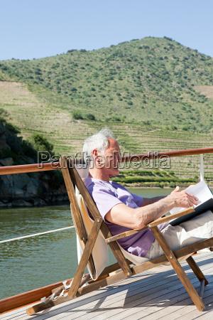 senior man reading book on a