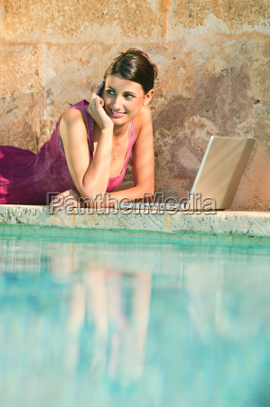woman lying by swimming pool with