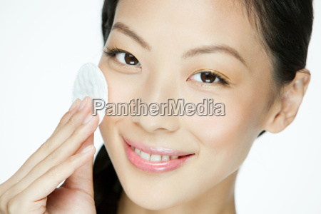 young woman using cotton pad on