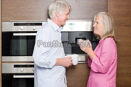 middle aged couple standing in kitchen
